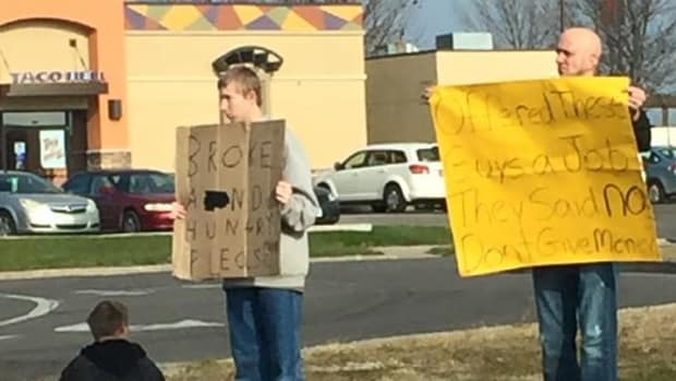 Mike Pothoff holding up sign next to beggars