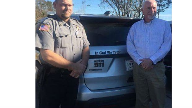 Beauregard Parish Sheriff Ricky Moses with a police cruiser adorning the nation's motto