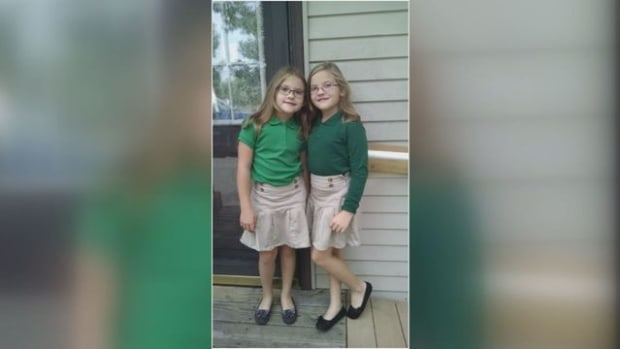 Kylie and Karlie holding green shirts