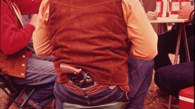 A man carrying a handgun.
