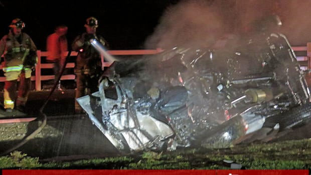 A firefighter douses the burning vehicle
