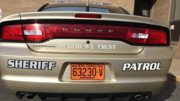 "Tan Dodge with ""In God, We Trust"" written on the back"