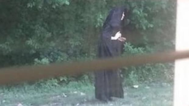 Community Looking For Answers After Photos Of Cloaked Figure Go Viral Promo Image