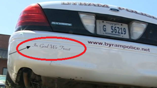 """Two sheriffs pose next to a patrol vehicle with """"In God We Trust"""" bumper sticker"""
