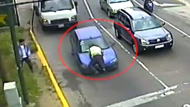 Traffic Cop Rides Hood Of Fleeing Car 1,000 Feet (Video) Promo Image