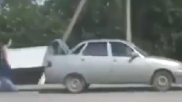Woman Runs Behind Car, Carries Refrigerator (Video) Promo Image