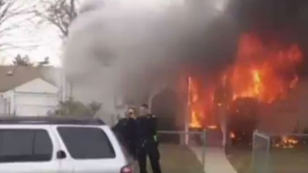Cops Take Smiling Selfie In Front Of Burning Home (Video) Promo Image