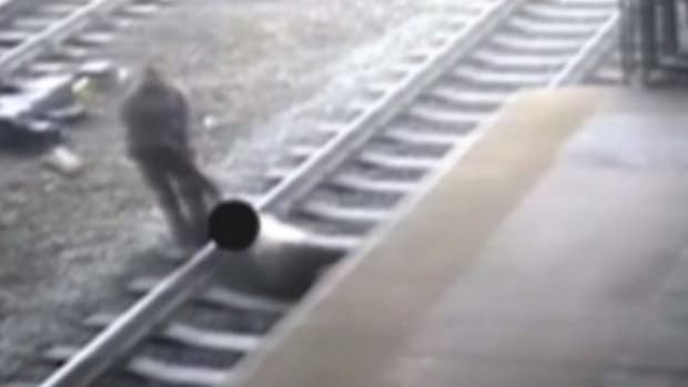 Cop Struggles To Save Man From Oncoming Train (Video) Promo Image