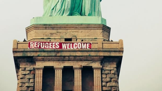 Activists Hang 'Refugees Welcome' Sign On Statue Of Liberty Promo Image