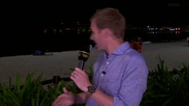 Reporter Stunned By Events Unfolding On Beach Behind Him (Video) Promo Image