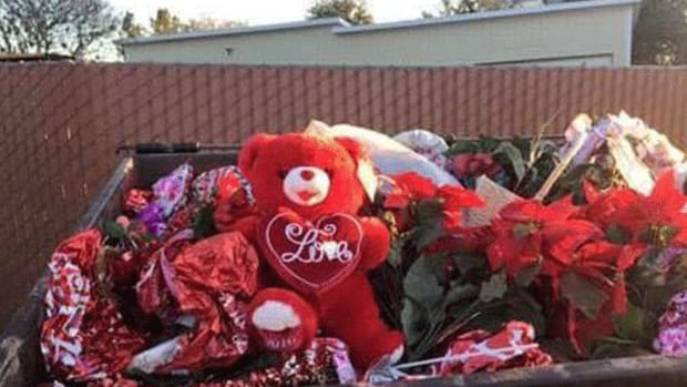Valentine's Day decorations in the dumpster at the cemetery