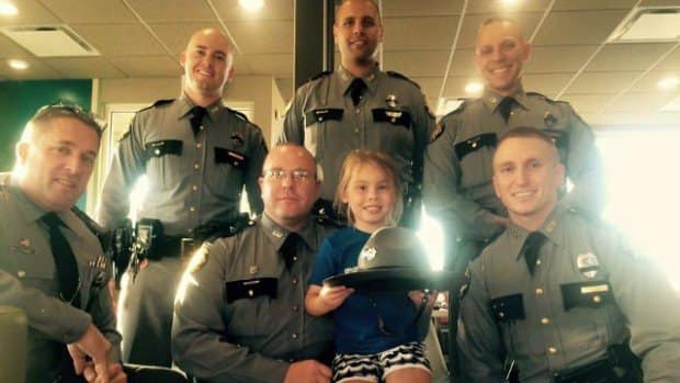 Troopers posing with 5-year-old girl