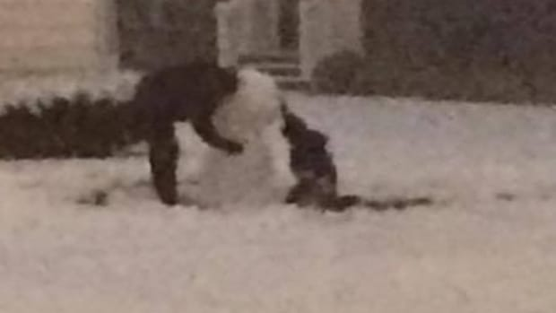 boy and police officer building snowman