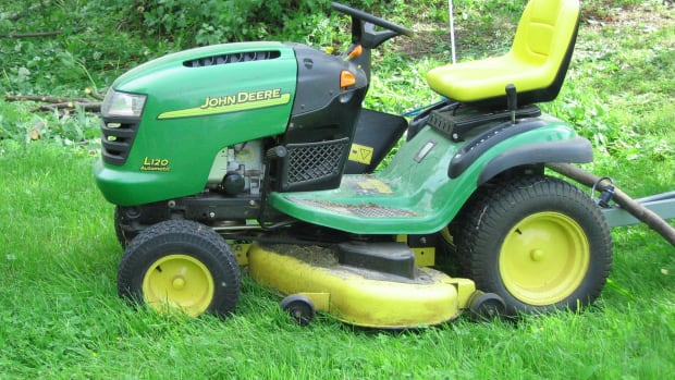 John Deere Lawn Mower On Uncut Grass.