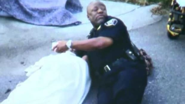 Lt. Joe Tucker comforts Johntez Byrd after a car accident
