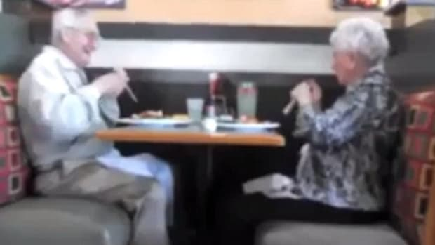 elderly couple goofing off with straws at a restaurant