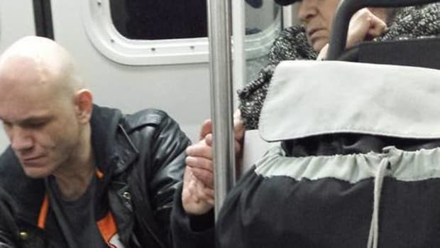 elderly woman holding stranger's hand on metro