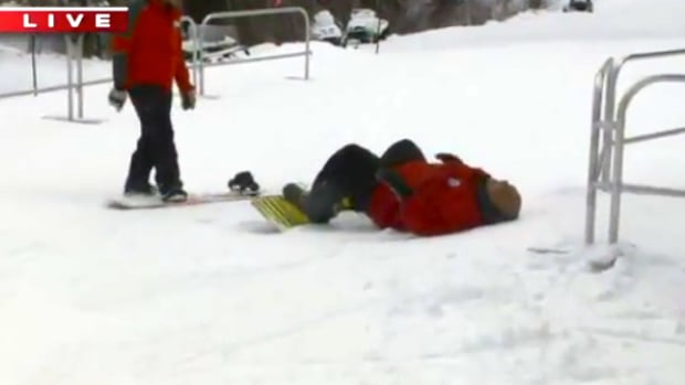 Big Budah falling after trying to high-five on snowboard