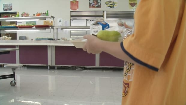 student holding tray in school cafeteria