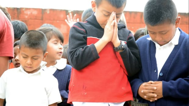 Students in Guatemala praying at school.
