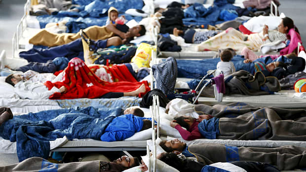 Refugees sleeping on camp beds on a running track in Hanau, Germany