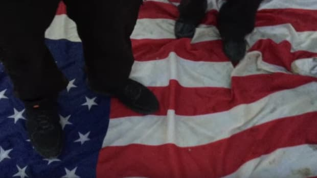 Trump Protesters Stomp On American Flag (Video) Promo Image
