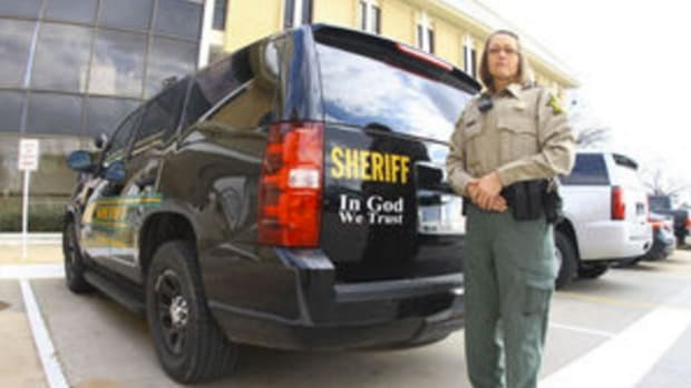 A deputy stands next to a patrol car with 'In God We Trust' displayed on it
