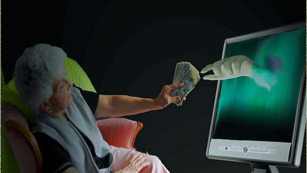 elderly woman handing money to computer (stock photo)