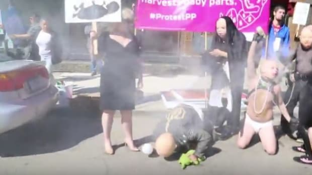 Adults Dressed As Babies Protest Pro-Lifers (Video) Promo Image