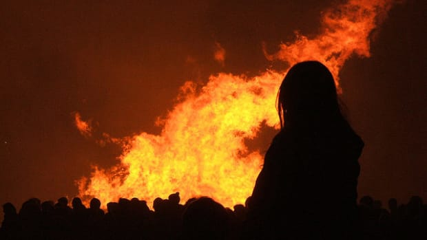woman stands in front of bonfire