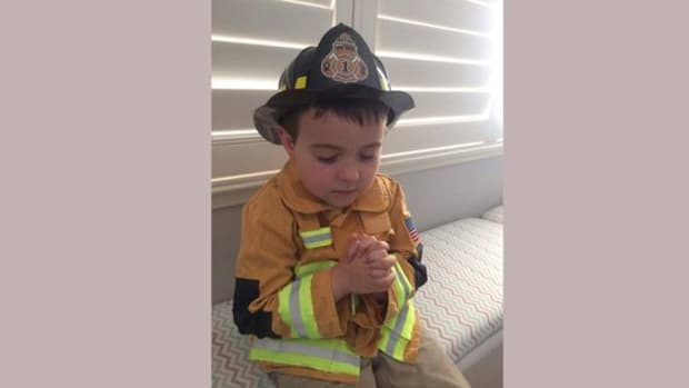 Brody praying in firefighter outfit