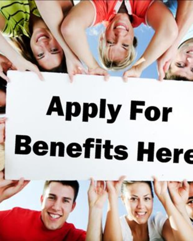 People holding up sign that reads 'Apply for Benefits Here'