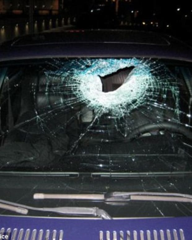 The windshield of a car is punctured and shattered after being hit with a brick