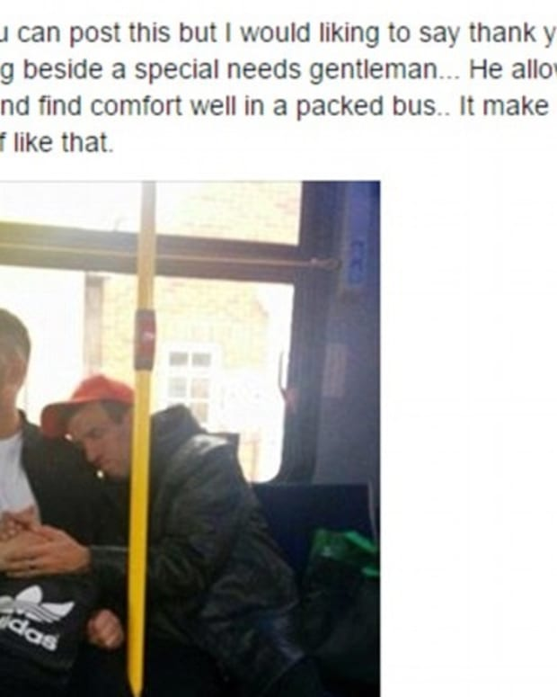 stranger holds special needs man's hand on bus