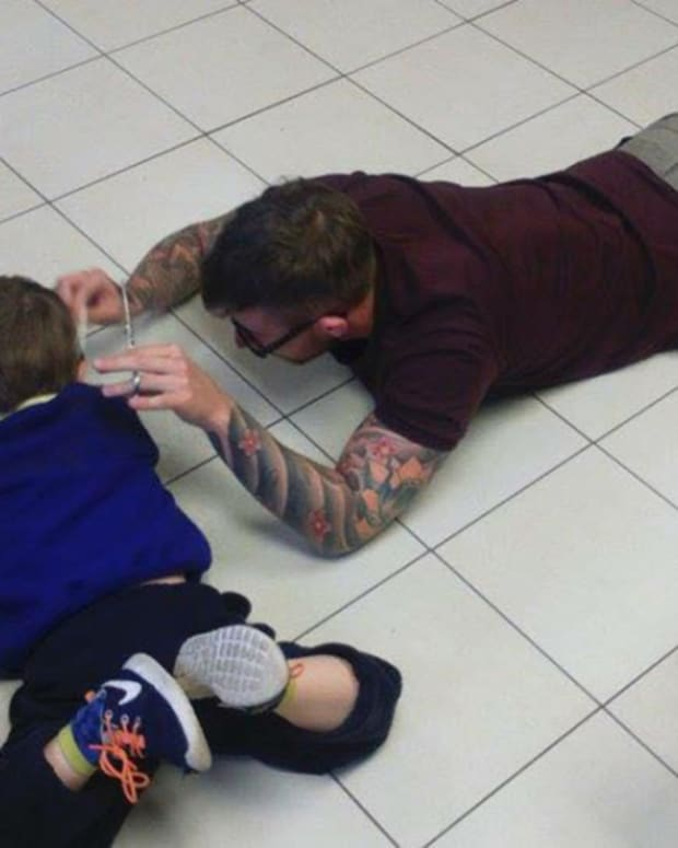 James Williams cutting Mason's hair on the floor