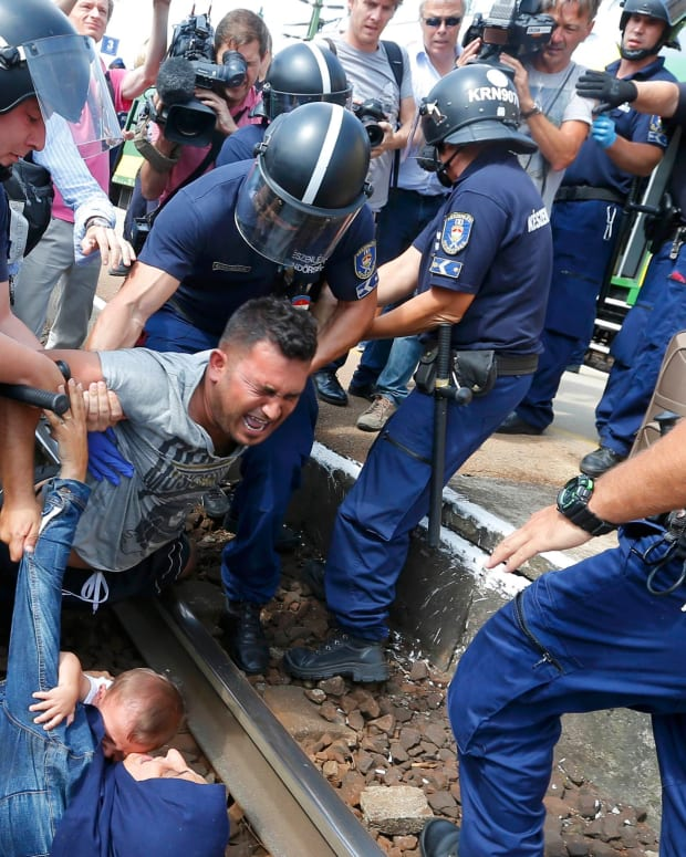 Hungarian policemen detain migrants on the tracks as they wanted to run away at the railway station in the town of Bicske, Hungary, camp for refugees and asylum seekers is located in Bicske. REUTERS/Laszlo Balogh