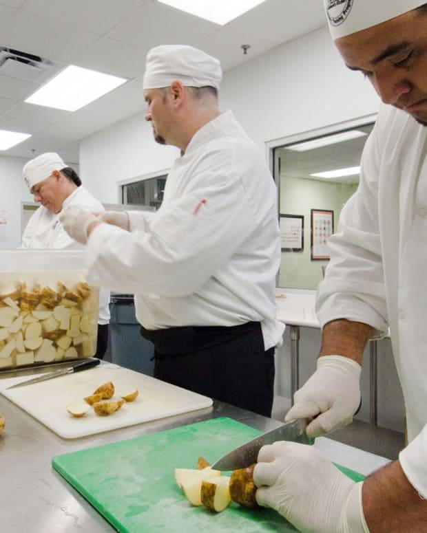man cutting potatoes