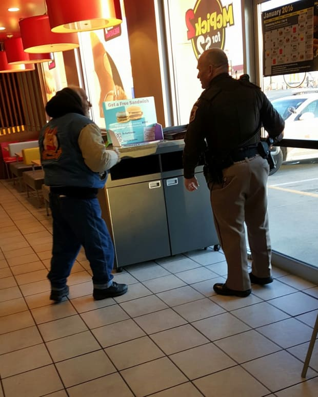 police officer talking to the homeless man in McDonald's