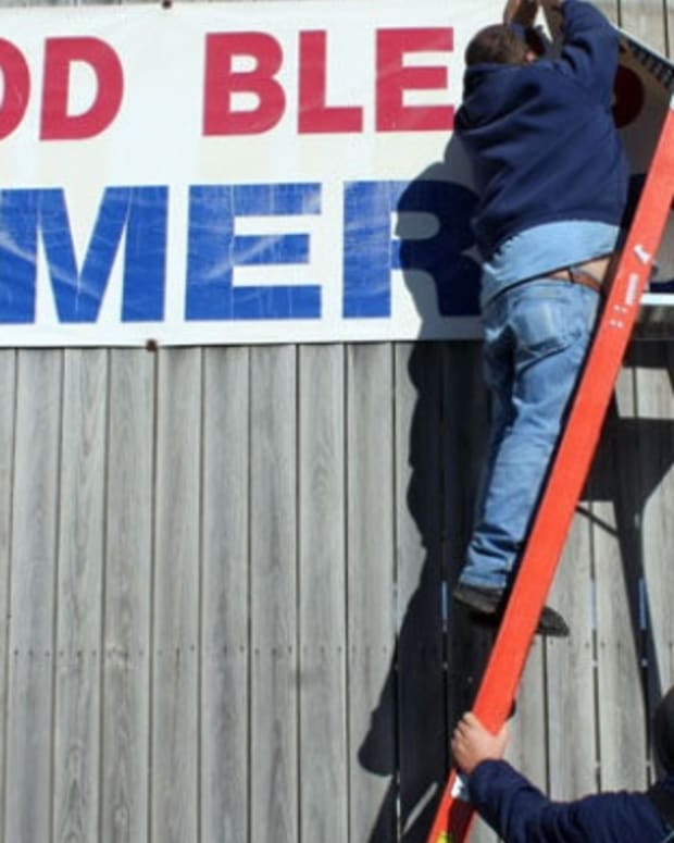 Workers Taking Down God Bless America Banner