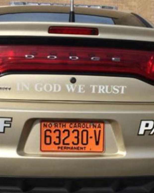"""Tan Dodge with """"In God, We Trust"""" written on the back"""