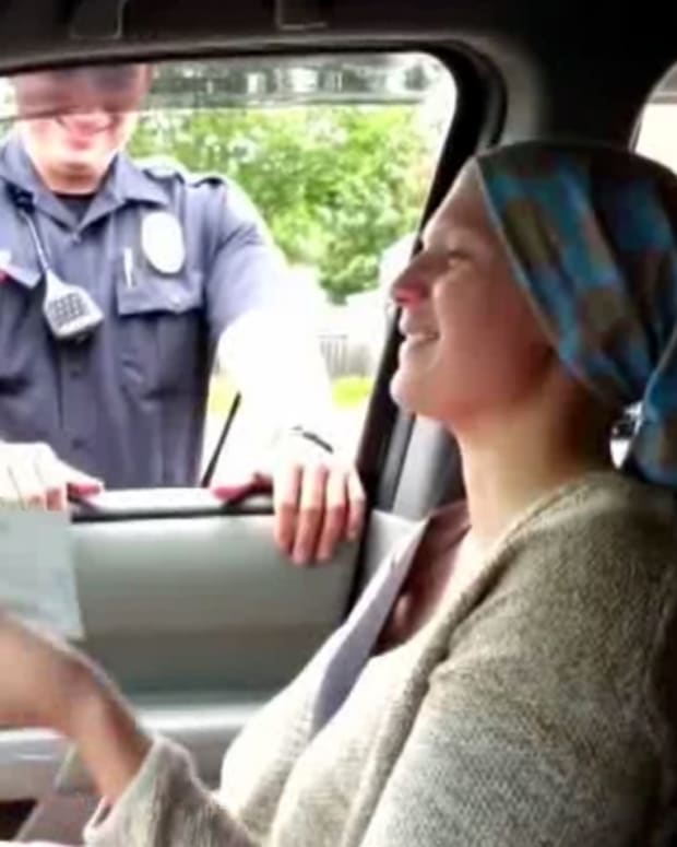 Maddie Carlson holding check that police officer gave her
