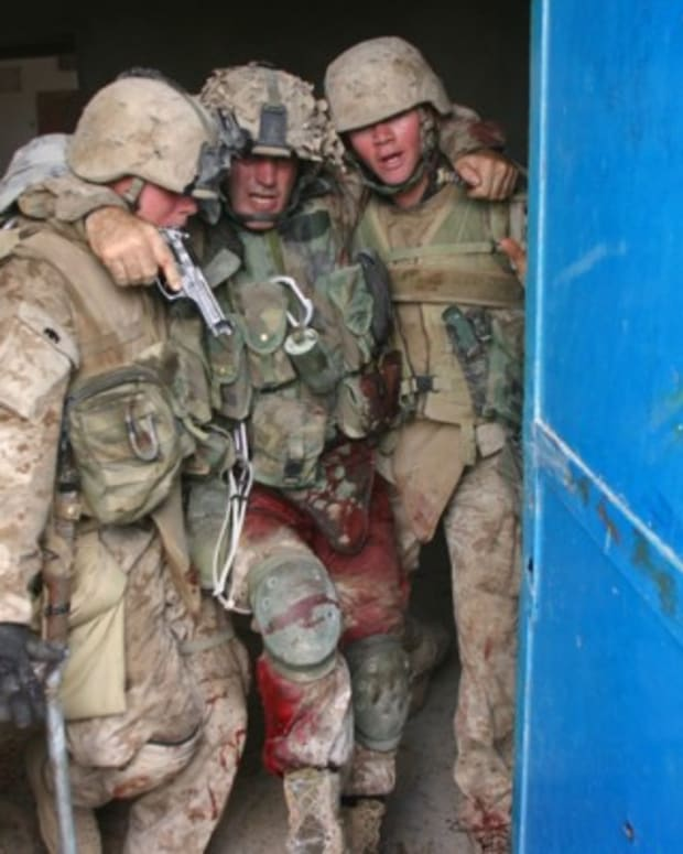 Chris Marquez and Dane Shaffer carry Sgt. Maj Brad Kasal to safety