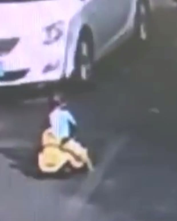 Toddler Rides Toy Bike In Rush Hour Traffic (Video) Promo Image