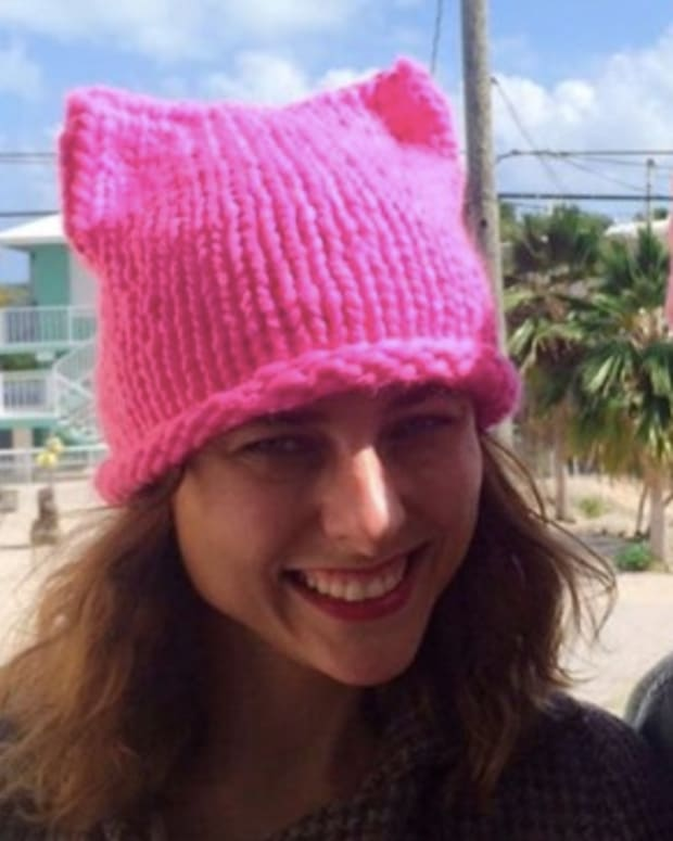 Here's Why Women Are Wearing Pink Knit Cat-Eared Hats Promo Image