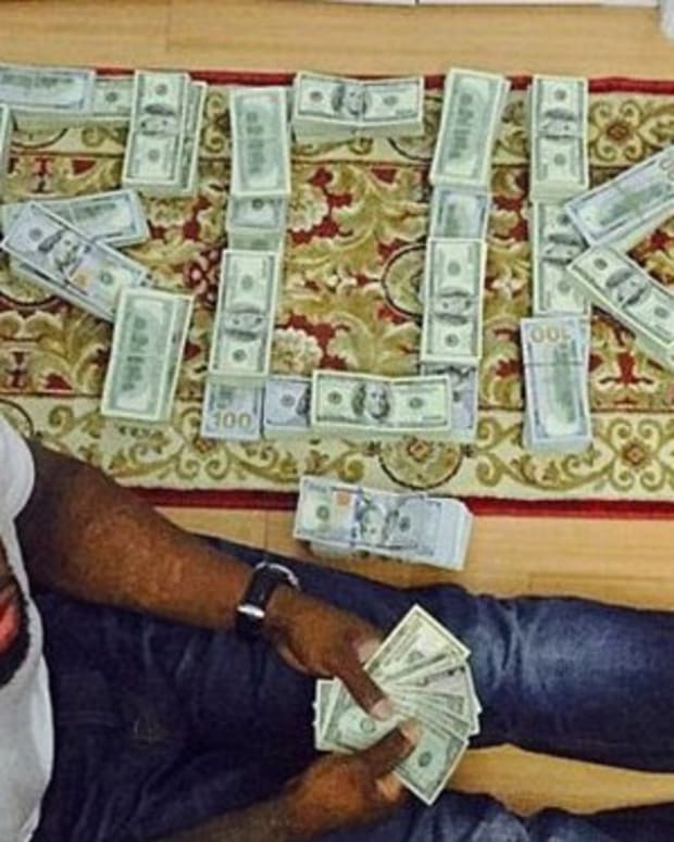 50 Cent with stacks of money