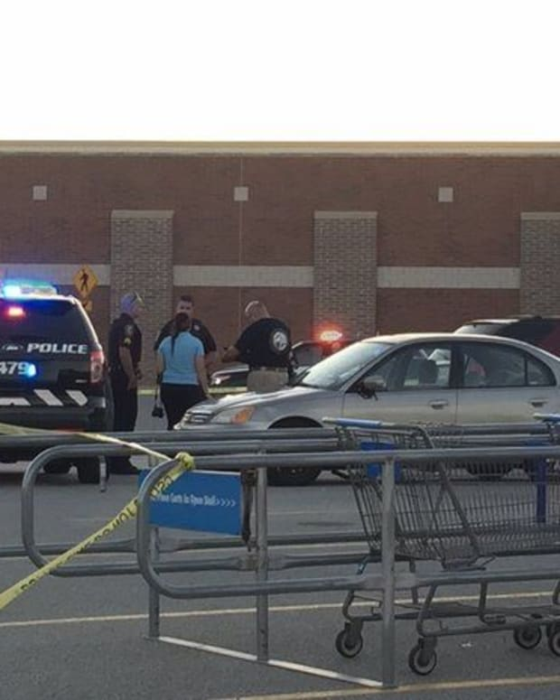 Investigators and police officers speak near car where baby was found in Walmart parking lot