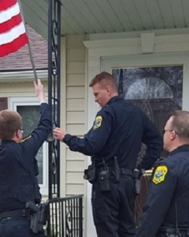 Police Officers Replace Elderly Widow's Stolen Flag Promo Image