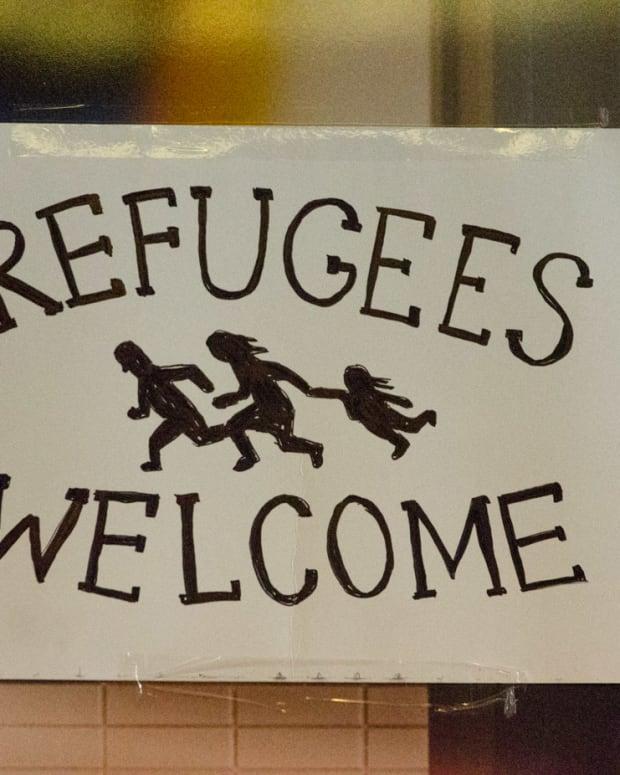 A sign welcoming asylum-seeking refugees