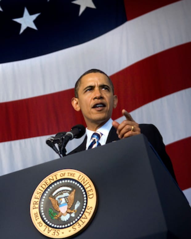 president obama speaking in front of american flag backdrop
