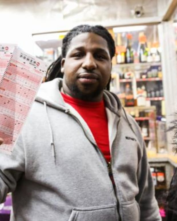 man holding up lottery tickets